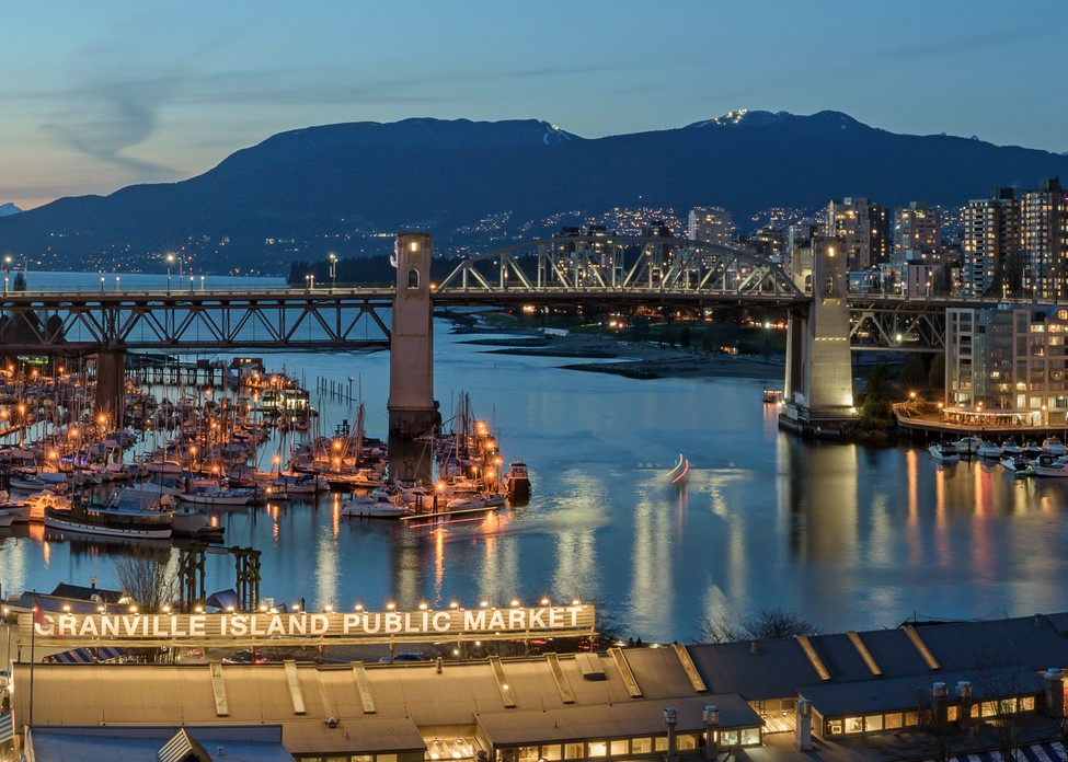 VANCOUVER, BRITISH COLUMBIA, CANADA - MARCH 30, 2018: Panorama of Downtown Vancouver, Burrard Street Bridge and Granville Island during sunset.